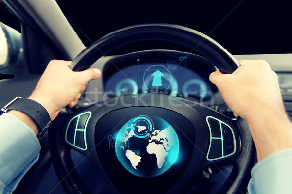 close up of man driving car with globe on screen Stock photo © dolgachov