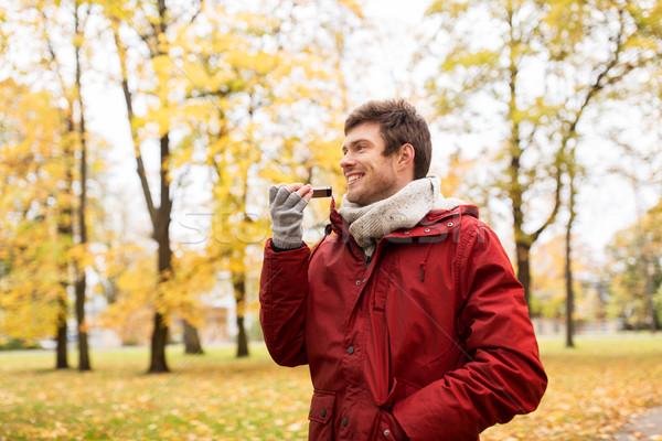 man recording voice on smartphone at autumn park Stock photo © dolgachov