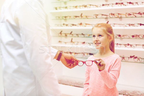 optician giving glasses to girl at optics store Stock photo © dolgachov