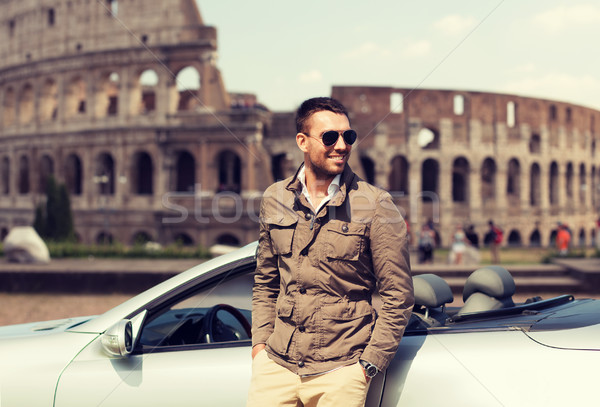 happy man near cabriolet car over coliseum Stock photo © dolgachov