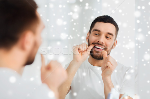 man with dental floss cleaning teeth at bathroom Stock photo © dolgachov