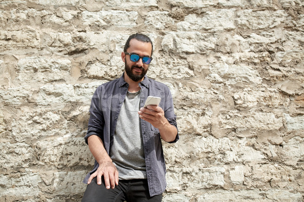 man texting message on smartphone at stone wall Stock photo © dolgachov