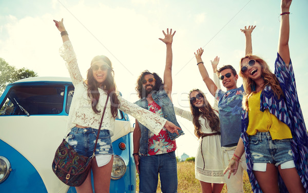 smiling hippie friends having fun over minivan car Stock photo © dolgachov