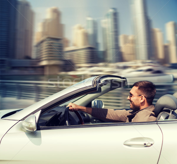 happy man driving cabriolet car on city  Stock photo © dolgachov