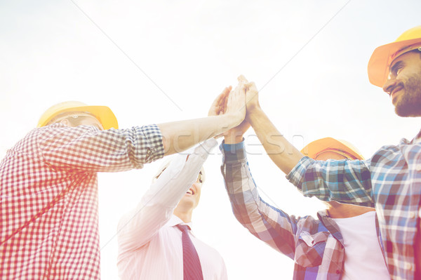 close up of builders in hardhats making high five Stock photo © dolgachov