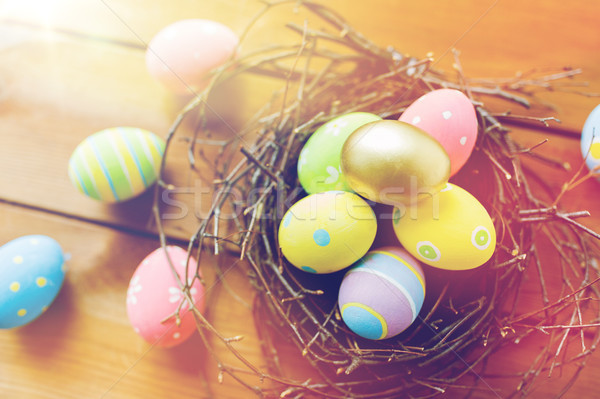 close up of colored easter eggs in nest on wood Stock photo © dolgachov