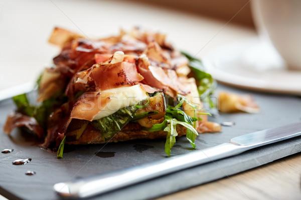 prosciutto ham salad on stone plate at restaurant Stock photo © dolgachov