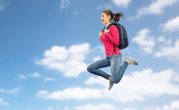 happy woman or student with backpack jumping Stock photo © dolgachov