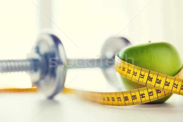 Stock photo: close up of dumbbell and apple with measuring tape