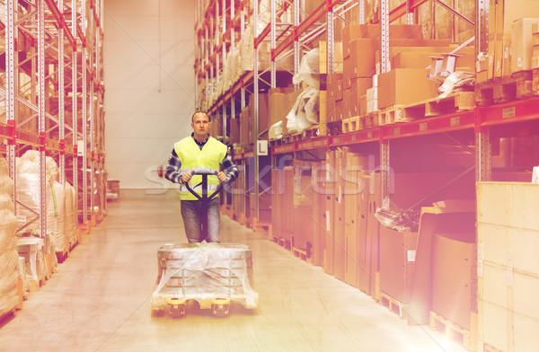 man carrying loader with goods at warehouse Stock photo © dolgachov