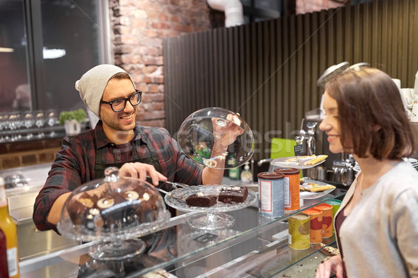 man or barman with cakes serving customer at cafe Stock photo © dolgachov