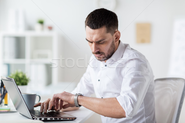 businessman with laptop and wristwatch at office Stock photo © dolgachov