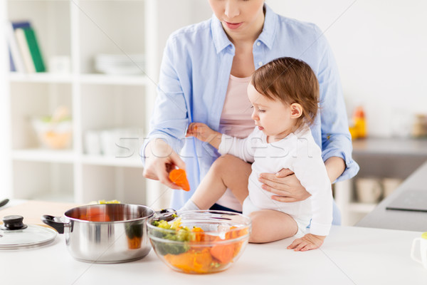 happy mother and baby cooking vegetables at home Stock photo © dolgachov
