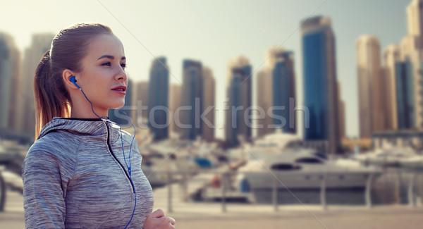 happy woman with earphones running over dubai city Stock photo © dolgachov