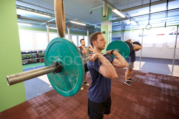 group of men training with barbells in gym Stock photo © dolgachov