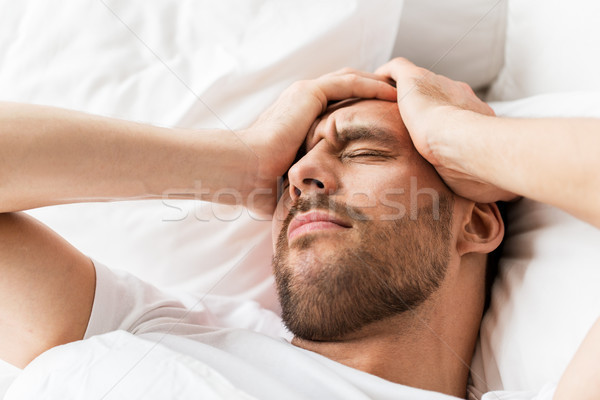 close up of man in bed suffering from headache Stock photo © dolgachov