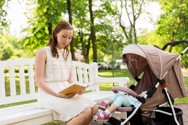 mother with child in stroller reading book at park Stock photo © dolgachov