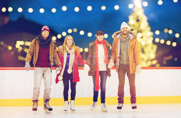 happy friends on christmas skating rink Stock photo © dolgachov