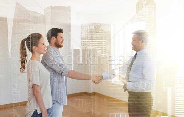man and realtor shaking hands at new home Stock photo © dolgachov