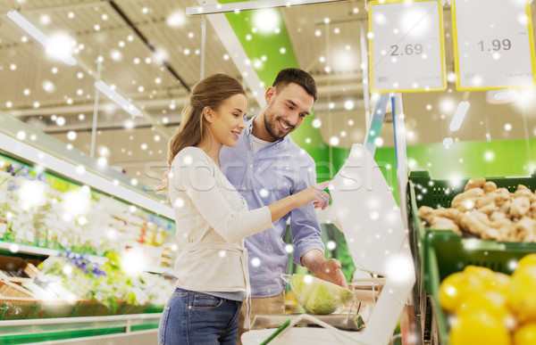 happy couple weighing cabbage on scale at grocery Stock photo © dolgachov