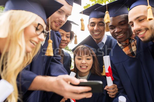 Diákok diplomások okostelefon oktatás érettségi technológia Stock fotó © dolgachov