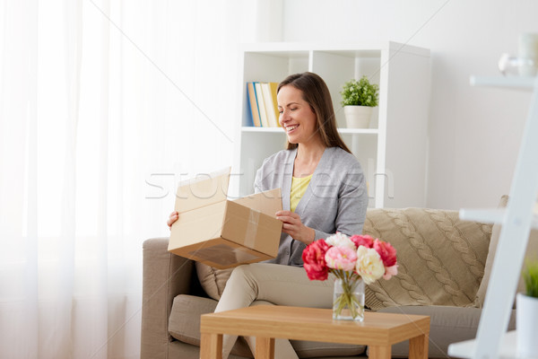 smiling woman opening parcel box at home Stock photo © dolgachov
