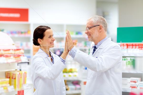 happy apothecaries at pharmacy making high five Stock photo © dolgachov