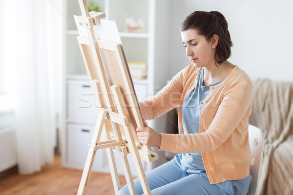 artist with easel drawing picture at art studio Stock photo © dolgachov
