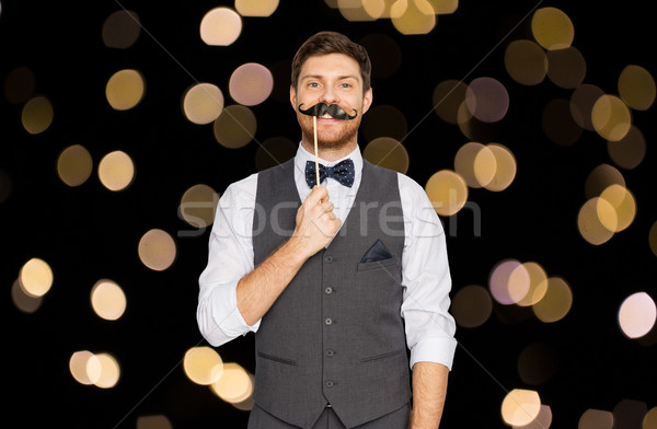 Stock photo: happy young man with fake mustache at party