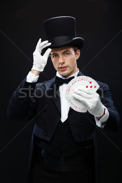 magician showing trick with playing cards Stock photo © dolgachov