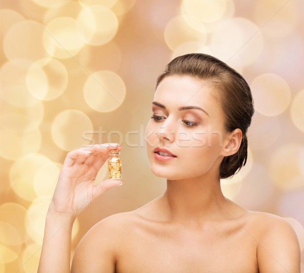 beautiful woman showing bottle with golden dust Stock photo © dolgachov
