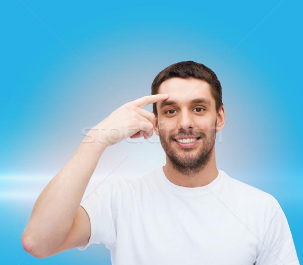 Souriant jeunes bel homme pointant front santé Photo stock © dolgachov