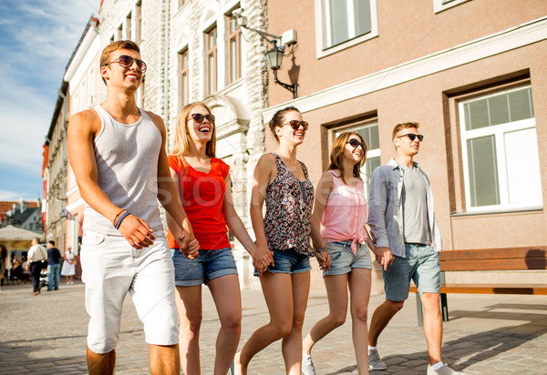 group of smiling friends walking in city Stock photo © dolgachov