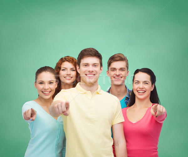 group of smiling teenagers over green board Stock photo © dolgachov