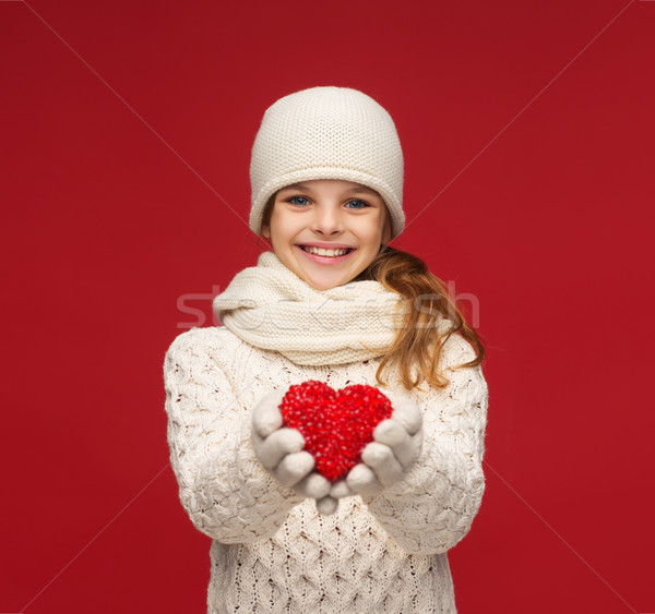 Stock photo: girl in winter clothes with small red heart