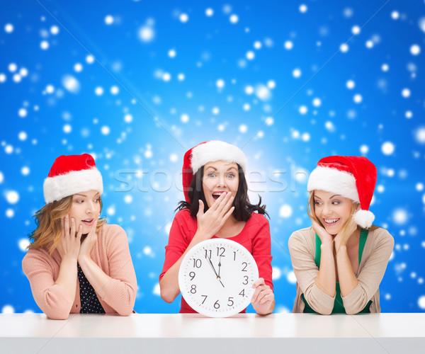 Uśmiechnięty kobiet Święty mikołaj pomocnik zegar Zdjęcia stock © dolgachov