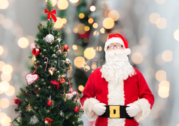 man in costume of santa claus with christmas tree Stock photo © dolgachov
