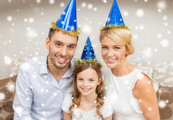 Stock photo: smiling family in party hats at home
