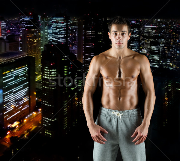 young male bodybuilder with bare muscular torso Stock photo © dolgachov