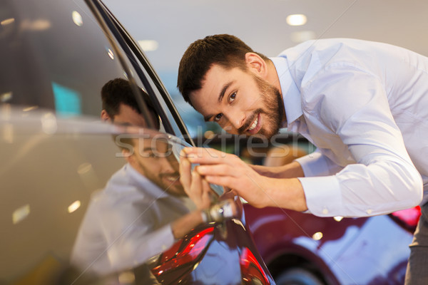 happy man touching car in auto show or salon Stock photo © dolgachov