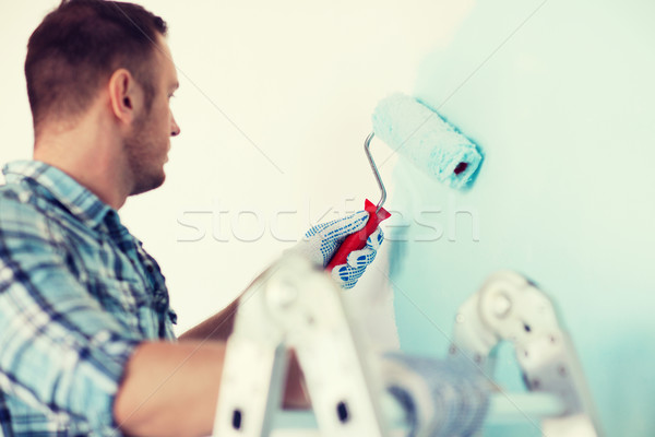 close up of male in gloves holding painting roller Stock photo © dolgachov