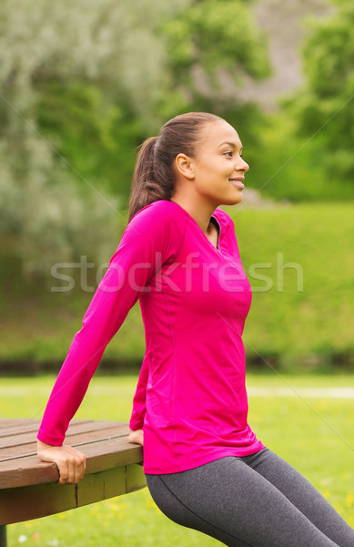 Stock photo: smiling woman doing push-ups on bench outdoors