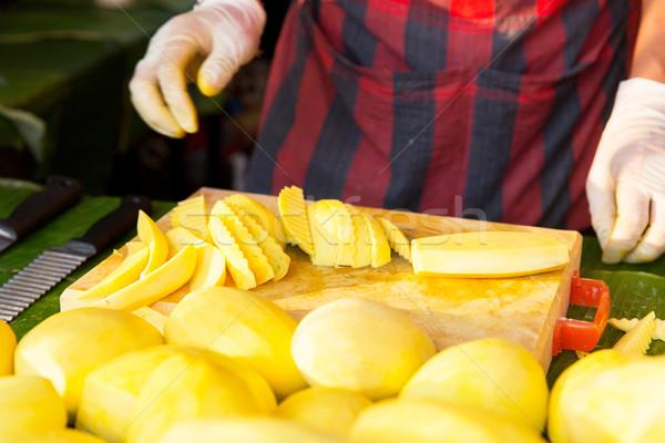 close up of cook hands and mango at street market Stock photo © dolgachov