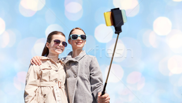 happy girls with smartphone selfie stick over blue Stock photo © dolgachov