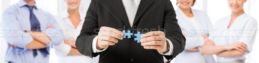 Stock photo: man matching puzzle pieces over business team