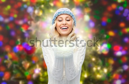 beautiful sexy woman in santa hat blowing on palms Stock photo © dolgachov