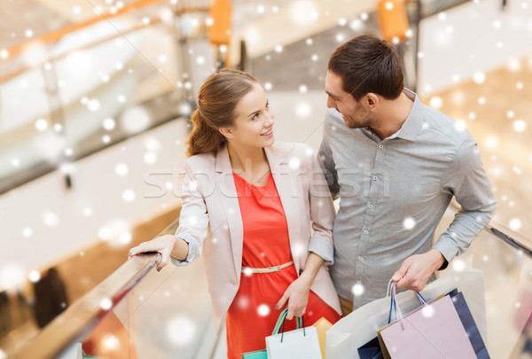 couple with shopping bags on escalator in mall Stock photo © dolgachov