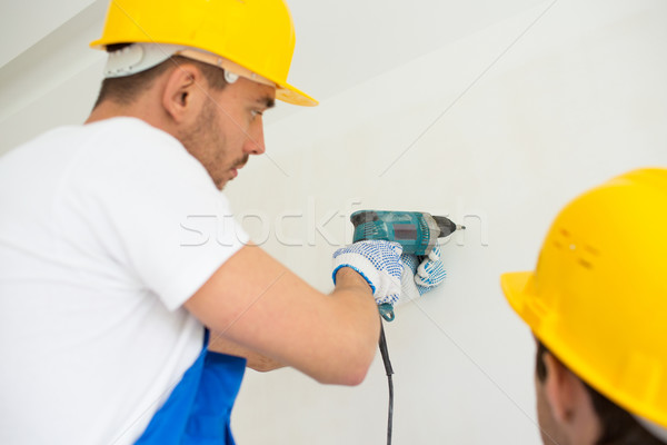 close up of builders with drill perforating wall Stock photo © dolgachov
