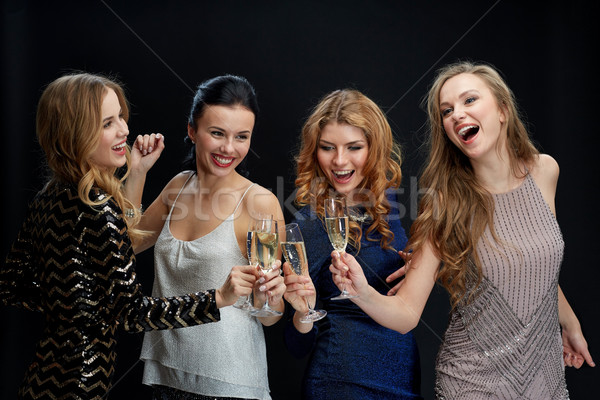 happy women clinking champagne glasses over black Stock photo © dolgachov