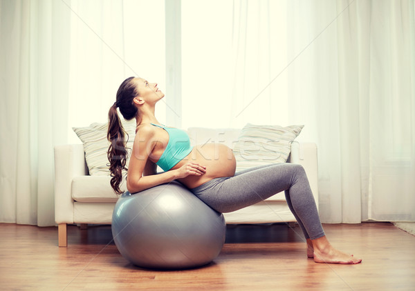 happy pregnant woman exercising on fitball at home Stock photo © dolgachov